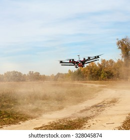 Copter flying at speed. Copter flying above the road and raises for a dust