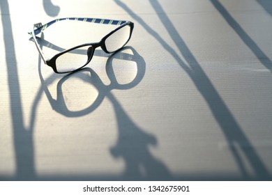 Copy space and abstract: white background with shadows from reading glasses