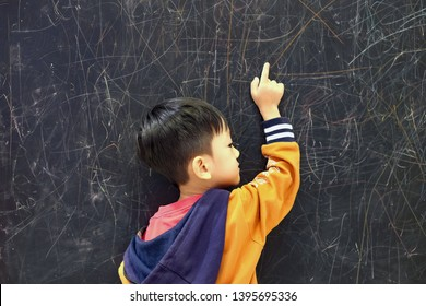 Copy space and back view of Asian kid 4 year old point to the backboard in classroom. Background with dirty white chalk at board, Concept back to school , education and leaning. Question and Answer.