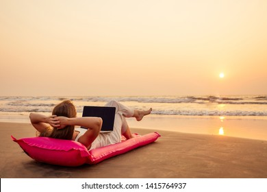 copy space Beautiful young woman working with laptop on the tropical beach. Happy traveling female using laptop on holidays, lyin down on pink inflatable mattress.remote work concept