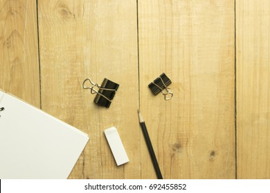 Copy space blank book and pencil and binder clip on wooden table. top view