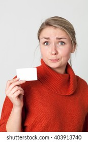 copy space card - embarrassed young blond woman holding a blank business or credit card in hand for presentation or payment, light grey background