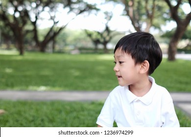Copy space and closeup Portrait Asian kid smile and look forward. Handsome boy playing in the park and turn the face to the left hand side. Background with green nature. Concept happy kid , play time.