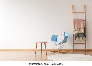 Copy space of empty wall in simple child's room with blankets on ladder, pillow on blue rocking chair, carpet and stool