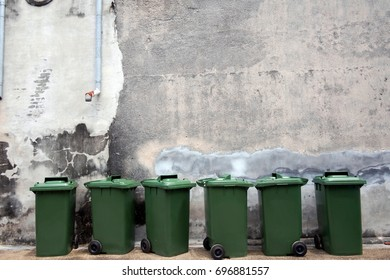 Copy space green plastic bins on old wall background
