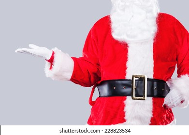 Copy space in hand of Santa. Traditional Santa Claus holding copy space while standing against grey background