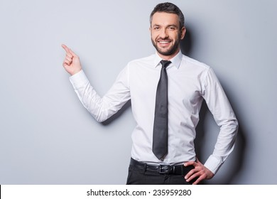 Copy space at his hand. Happy mature man in shirt and tie pointing copy space and smiling while standing against grey background