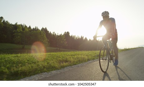 COPY SPACE, LENS FLARE: Professional male road biker enjoying a sunny cruise on his bicycle. Active man with sunglasses racing in a professional road bicycle race through sunny spring countryside.