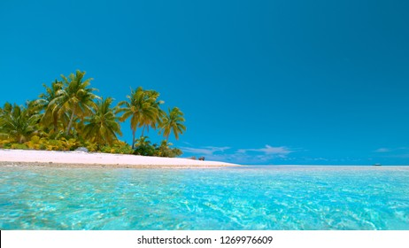 COPY SPACE, LOW ANGLE: Picturesque view of the pure ocean and the idyllic exotic island in the vast Pacific. Tranquil tropical sea surrounds the beautiful white sandy shoreline of One Foot Island.