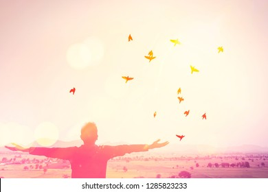 Copy space man raise hand up on top of mountain and sunset sky with birds fly abstract background. Freedom travel adventure and business victory concept. Vintage tone filter effect color style.