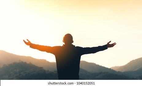 Copy space of man rise hand up on top of mountain and sunset sky abstract background. Feel good freedom and travel adventure concept. Vintage tone filter effect color style.