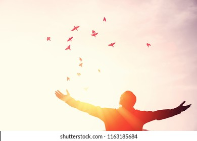Copy space man rise hand up on top of mountain and sunset sky with birds fly abstract background. Freedom travel adventure and business victory concept. Vintage tone filter effect color style.