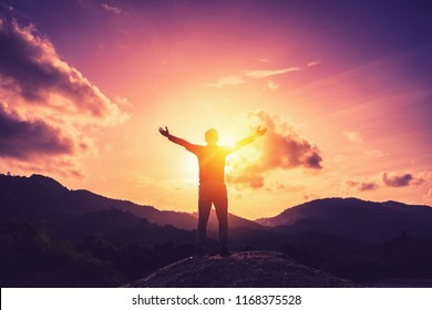 Copy space of man rise hand up on top of mountain and sunset sky abstract background. Freedom and travel adventure concept. Vintage tone filter effect color style.