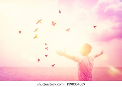 Copy space of man rise hand up on sunset sky at beach and island double exposure birds fly colorful bokeh abstract background. Freedom and travel adventure concept. Vintage tone filter color style.