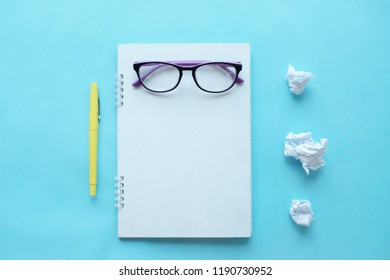 copy space notbook and pen  glasses  on blue background. space for text