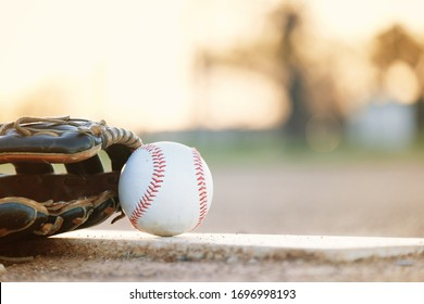 Copy space on blurred background by baseball with glove, laying on sports field.