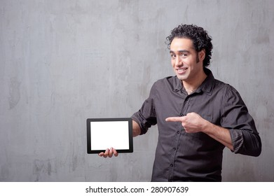 Copy space on his tablet. Handsome young Arabic man holding digital tablet and pointing it with smile while standing against grey background