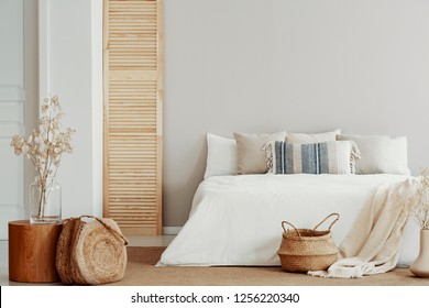 Copy space on white empty wall of natural bright bedroom with natural accents