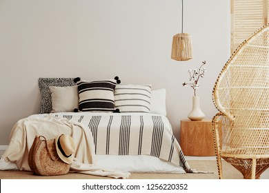 Copy space on white empty wall of bright trendy bedroom with flower in vase on wooden nightstand, king size bed with striped bedding and rattan peacock chair