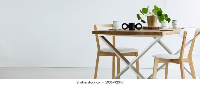 Copy space on white wall in empty dining room interior with chairs at wooden table