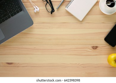 Copy space on wooden desk with laptop, glasses, headphones, pen, notebook, coffee, smart phone and apple
