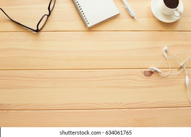 Copy space on wooden table with glasses, notebook, a cup of coffee and headphones
