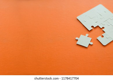 Copy space orange color with white jigsaw puzzle pieces.