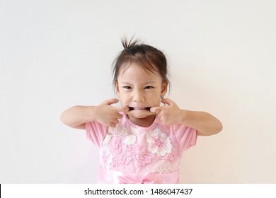 Copy space and portrait Asian girl 3 year making angry face. Asia kid pretend to giant and open mouth by finger. Cute Asia girl try to making funny face. Concept kid imagine. imagination and playing.
