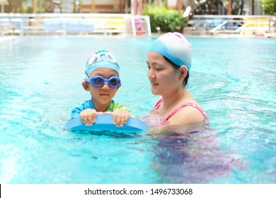 Copy space and portrait beautiful Asian mother wearing swimming suite and try to teaching her kid swimming in the pool. Little Boy using foam swimming. concept family activity , Sport and education.