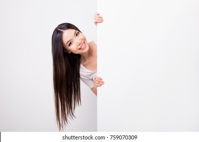 Copy space portrait of charming attractive girl hiding, standing behind empty white vertical wall isolated over white background