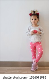 Copy space and Portrait cute Asian girl 3 year old wear reindeer headband. Beauty model Asia kid stand at white wall and pose with relax activity. Concept celebration and Happy, Love Christmas party,