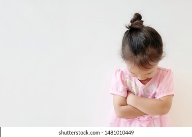 Copy space and portrait little Asian girl 3 year old punished. Asia kid cross her arm and face down to accept a mistake. Concept punish kid and time out limit, Rule and punishment,  problem and handle
