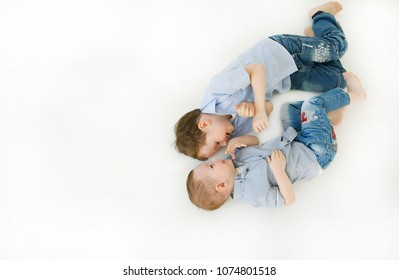 Copy space. Portrait of two cheerful and positive little boys playing with a laugh and tickling each other with smiles, lying on the floor isolated on white background. friendly brothers. Childhood