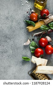 Copy space. Raw Pasta ingredients. Cherry-tomatoes, spaghetti pasta, garlic, basil, parmesan and spices on dark grunge background