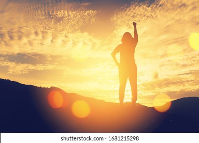 Copy space of silhouette woman raise hand up on top of mountain and sunset sky cloud abstract background. Freedom feel good and travel adventure holiday concept. Vintage tone filter effect color style