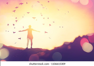 Copy space of silhouette woman rise hand up on top of mountain and sunset sky with birds fly abstract background. Freedom and travel adventure concept. Vintage tone filter effect color style.