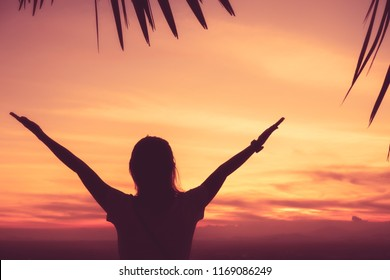 Copy space of silhouette woman rise hand up on top of mountain and sunset sky with palm leaf abstract background. Freedom and travel adventure concept. Vintage tone filter color style.