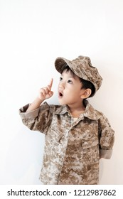 Copy space and soft focus Asian boy wear soldier suit, Portrait junior commander wear military uniform look forward and he think and explain. White background. Concept Dream, passion, indoctrination.