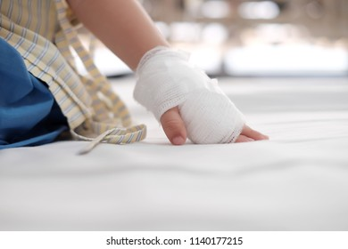 Copy space and Soft focus at bandage cover on baby hand and Saline intravenous on hand. The kid wearing patient clothing and put his hand on sickbed. Concept of recovery kid, medical treatment,
