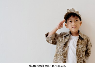 Copy space and soft focus at little Asian kid 5 year old smile and wear soldier suit, Portrait handsome boy wear military uniform and stand at salute. clasped behind back. concept dream and occupation