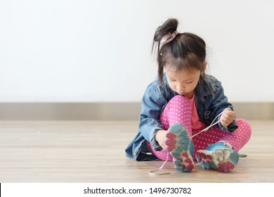 Copy space and Soft focus portrait cute little Asian girl 3 year old sit on the ground and try to tie her shoes. Beautiful kid try to shoelace by herself. concept first step , growth up and moving on.