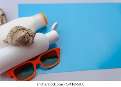 Copy space of summer. Light blue background. Sun cream, orange sun glasses, shells.