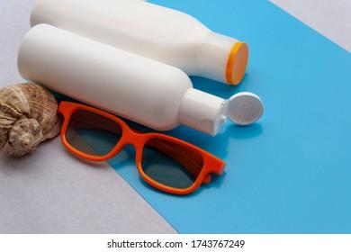 Copy space of summer. Light blue background. Sun cream, orange sunglasses, shells.