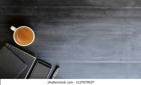 Copy space top view workspace with book and pen coffee cup on black office desk work wooden texture.