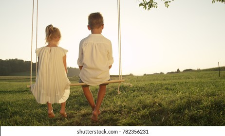 COPY SPACE: Two young children sitting on wooden swing gazing at the sunset. Little brother and sister enjoying a golden summer evening. Blooming love between boy and girl swinging on a swing set.