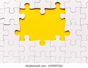 Copy space of unfinished white jigsaw puzzle pieces. One missing jigsaw piece on yellow background