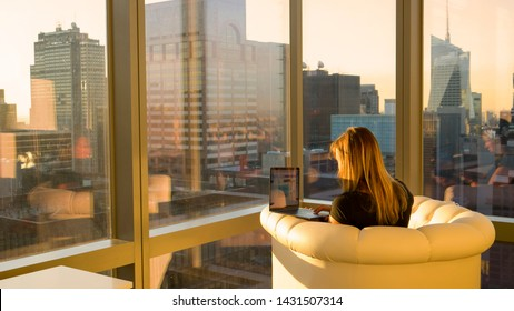COPY SPACE: Unrecognizable woman working on her computer from her home office facing the spectacular metropolitan city at sunrise. Businesswoman doing research from a luxury hotel room in New York.