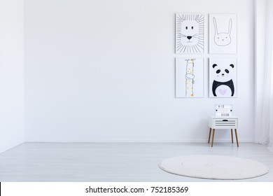 Copy space of white spacious autistic kid's room with drawings, white cabinet and carpet