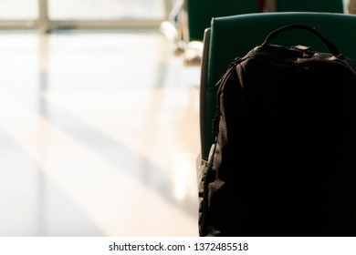 Copy space window light through Airport boarding terminal with black pack bag on seat for travel insurance concept