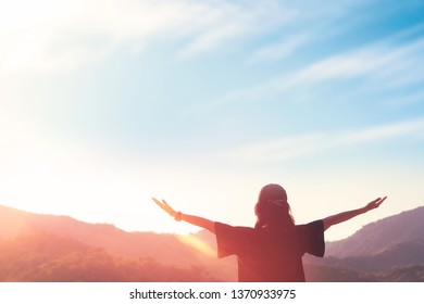 Copy space of woman raise hand up on top of mountain and sunset sky abstract background. Freedom feel good and travel adventure holiday concept. Vintage tone filter effect color style.